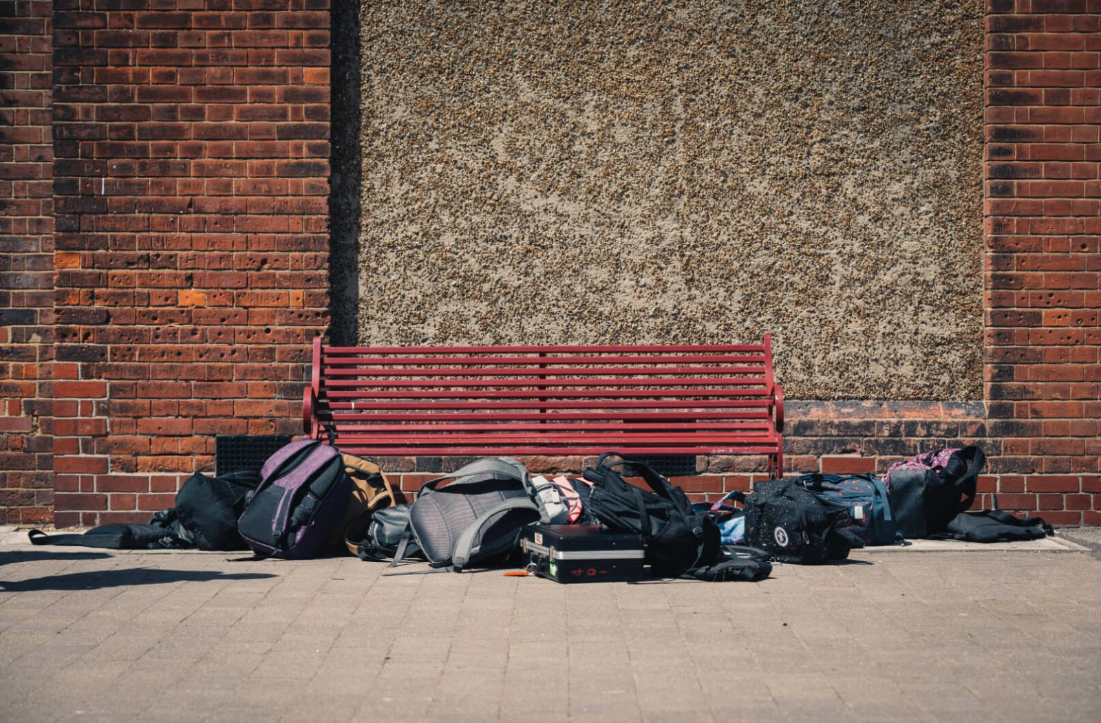 Image of schoolbags left by a bench in a school playground