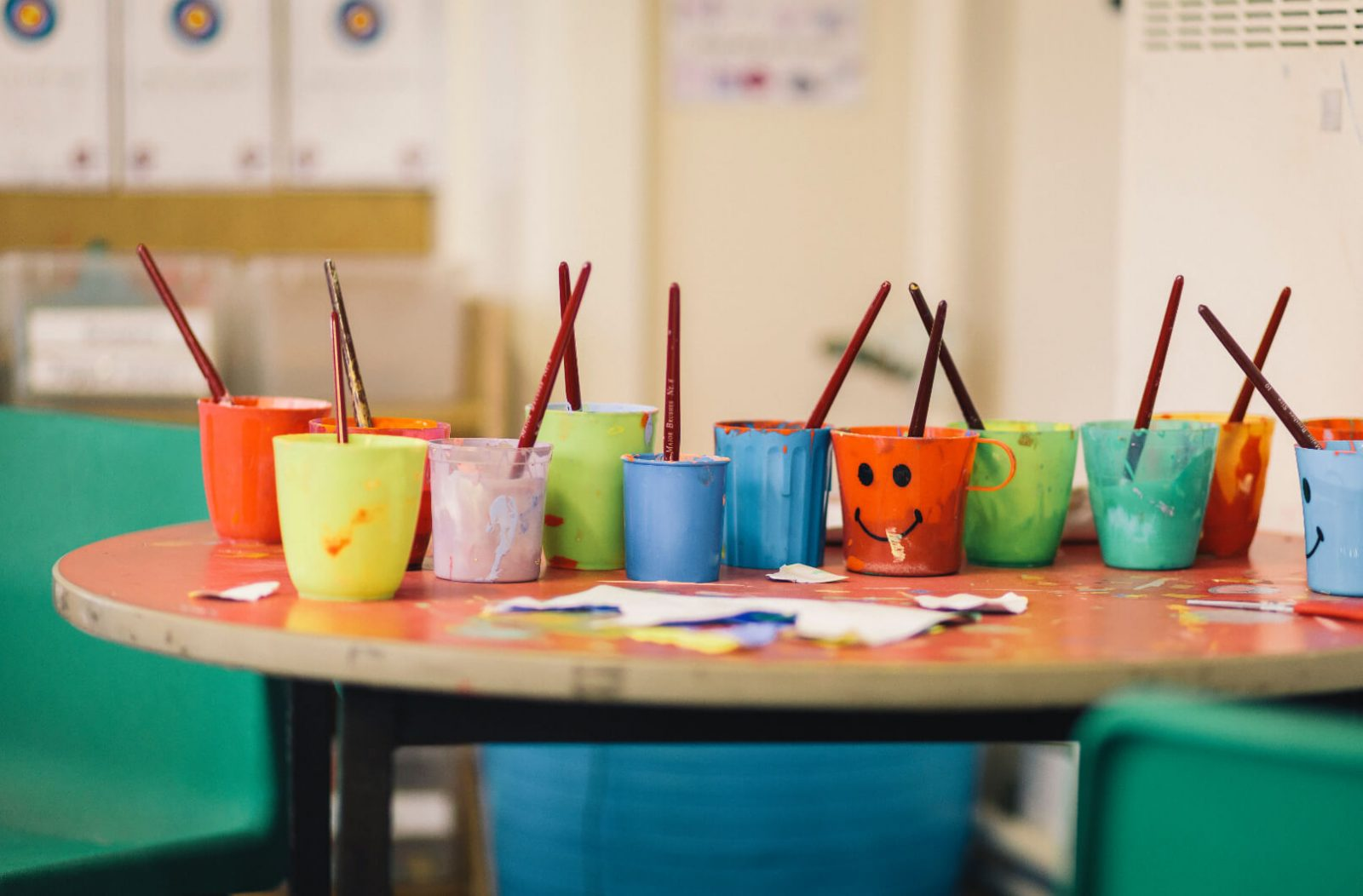 Image of pots of poster paint for creative expression in schools