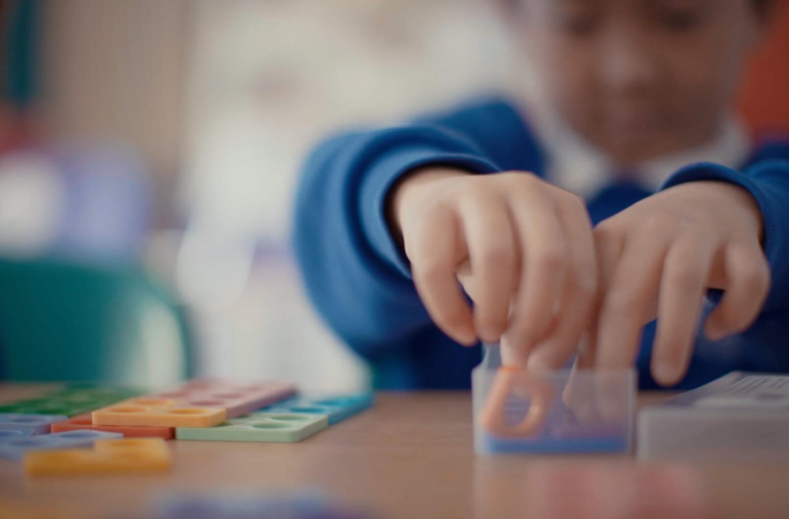 Image of child creating images using coloured plastic shapes